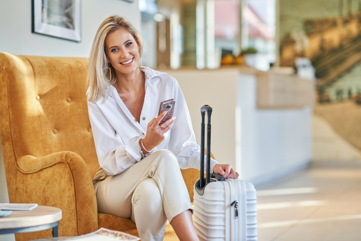 A travelling personal assistant sitting in an airport lounge with suitcase